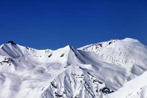 off-piste besneeuwde helling en blauwe heldere hemel foto