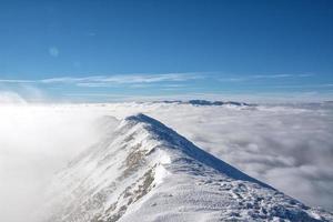 alpine landschap met pieken vallende sneeuw en wolken foto