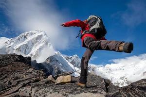 wandelaar springt in de Himalaya-bergen foto