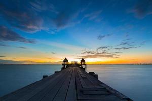 oude brug over zee in zonsondergang met mooie hemel