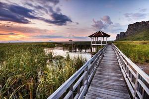 zonsondergang op houten pad op de moerassen in de buurt van de berg.