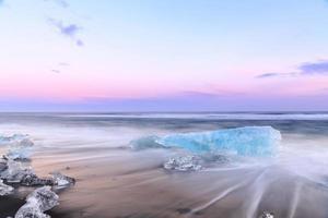 ijs op het zwarte vulkabische zandstrand foto
