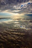 weerspiegeling van dramatische hemel op het strand van nusa dua, bali, indonesië