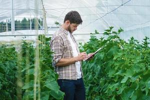 man met de tablet inspecteert langzaam planten.