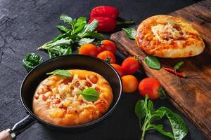 pizza in een pan en een andere op een houten dienblad foto