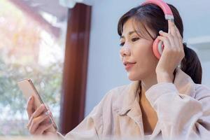 Aziatische vrouw luisteren naar muziek foto