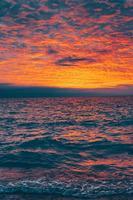 heldere zonsondergang over kabbelende oceaan foto