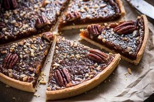 snijden van pecannoot taart, op houten tafel foto