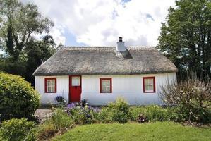 Iers huisje met een rieten dak van stro en een weelderige tuin