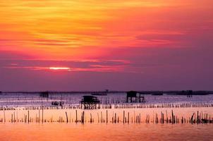 silhouet van Thais vissershuis bij zonsondergang