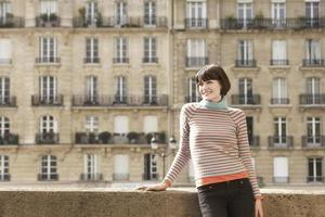 lachende vrouw op brug tegen herenhuizen