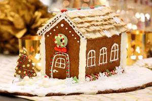 Kerst peperkoek huis op de gedecoreerde tafel foto