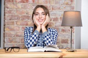 gelukkig mooie vrouw zittend aan tafel met boek