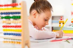 klein meisje huiswerk thuis foto
