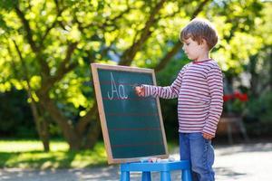 kleine jongen op schoolbord het beoefenen van wiskunde foto
