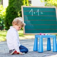 kleine jongen op blackboard leren schrijven foto