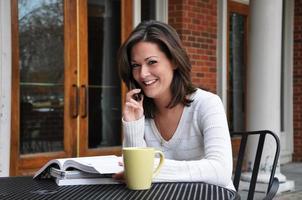 vrouwelijke student studeert met handboeken en mobiele telefoon foto