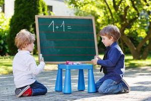 twee siblinig jongens op schoolbord wiskunde oefenen foto