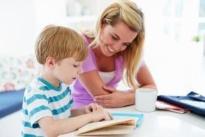 moeder helpt zoon met huiswerk in de keuken foto