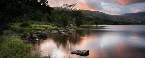 panorama landschap prachtige zonsopgang boven meer met bergen foto