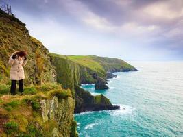 Ierse atlantische kust. vrouw toerist die zich op rotsklif bevindt