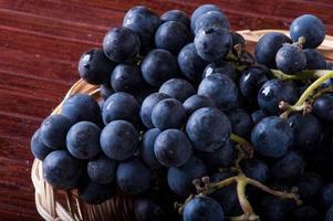 mand met zwarte druiven foto