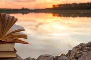 stapel hardcover boek, open boek over wazig natuurlandschap