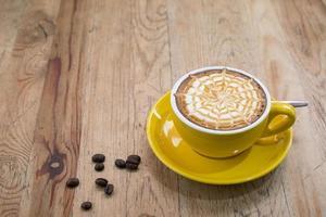 een latte koffie op een houten bureau