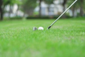 golfbal en club in golfbaan foto