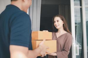 het bezorgen van pakketten aan de vrouw thuis foto