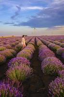 meisje wandelen in een lavendelveld tijdens zonsondergang foto