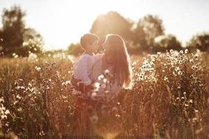 gelukkige moeder communicatie met zoon in een tarweveld foto