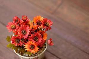 kunstbloemen in kleine pot op houten tafel.