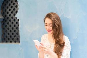 lachend schattig meisje tijdens het chatten op haar telefoon