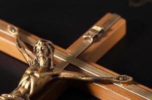 kruisbeeld met Jezus op zwart lederen bijbel