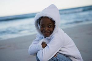meisje gehurkt op het strand bij zonsondergang foto