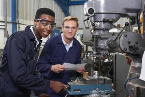 ingenieur toont leerling hoe boor in fabriek te gebruiken