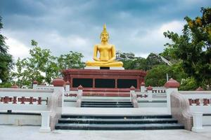 Boeddhabeelden op blauwe hemel vóór het vooraanzicht van de regen foto
