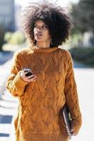 portret van aantrekkelijke afro vrouw met behulp van mobiele telefoon in de straat foto
