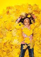 klein Afrikaans meisje bedekt met herfstbladeren