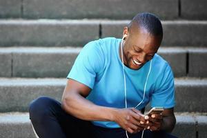 glimlachende man die naar mobiele telefoon kijkt en naar muziek luistert