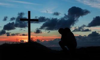 zonsondergang biddende man kruis foto
