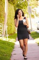 vrouw die langs straat loopt om te werken met behulp van mobiele telefoon