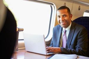 zakenman die aan trein aan het werk pendelt en laptop met behulp van