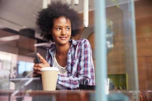 zakenvrouw op telefoon met behulp van digitale tablet in coffeeshop foto