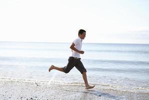 jongen loopt op blote voeten op het strand