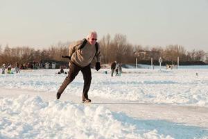 nederlands winterlandschap met schaatser op bevroren meer.