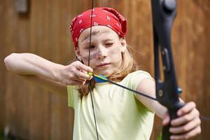 meisje boogschutter met boog schieten naar sport doel foto