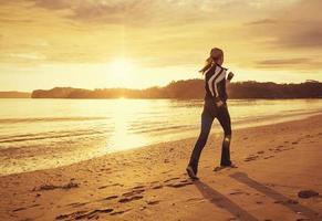 gezonde vrouw draait op het strand bij zonsondergang