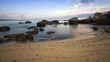 lucht, rotsen, zee en zandstrand.